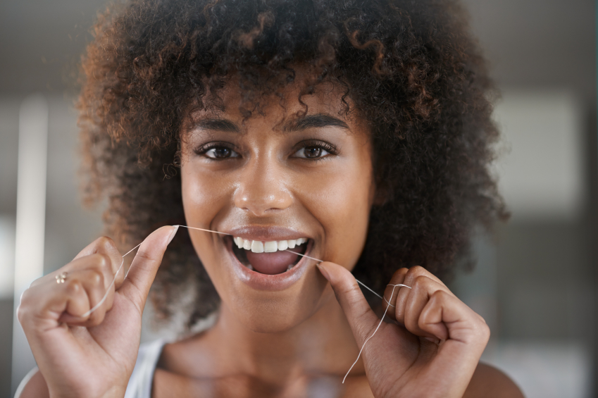 A flossing woman who is ecstatic over the The Benefits of Dental Implants in Portland, OR